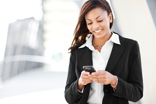 A shot of a beautiful black businesswoman texting